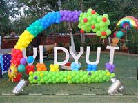 Baby name cutout with a rainbow balloon arch for a 1st birthday party