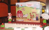 A Barnyard scene setter with a wooden fence for the stage decor for a little girls 2nd birthday party. The scene has all the elements of a farm - a barn, Cow, Horse, a Farmer, Pig, Sheep, duck and ducklings and the farm dog.